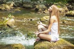 girl meditating river